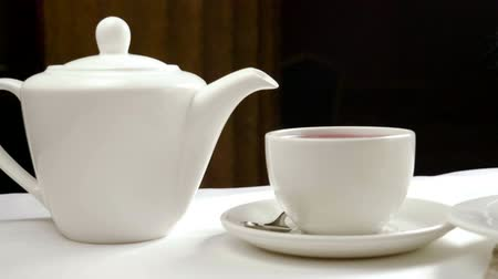 bica : Tea break. Close-up shot of ceramic teapot and teacup. Slow motion. HD