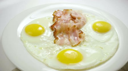 cholesterol : Close-up shot of three fried eggs and bacon serving on a white plate for breakfast. Slow motion. HD