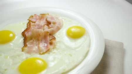 omlet : Close-up shot of three fried eggs and bacon serving on a white plate for breakfast. Slow motion. HD