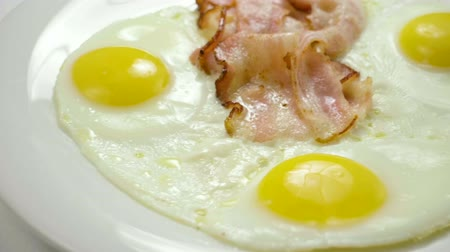 служить : Close-up shot of three fried eggs and bacon serving on a white plate for breakfast. Slow motion. HD