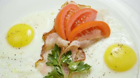 служить : English breakfast. Close-up shot of three fried eggs and bacon serving on a white plate. Slow motion. HD
