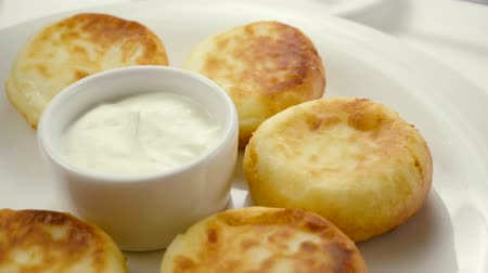 queijo : Close-up shot of five cheesecakes and sour cream on a white plate. Slow motion. HD