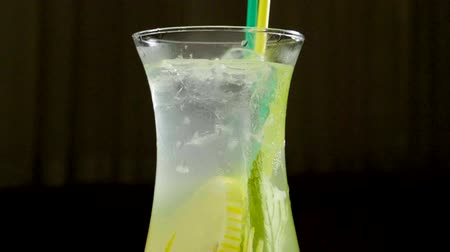 limonada : Close-up shot of ice being thrown into a glass of lemonade on black background. Slow motion. HD Stock Footage