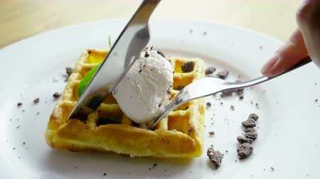 блин : Eating Breakfast. Close-up shot of womens hands cutting viennese waffles with a knife and fork. 4K