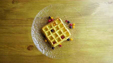 клюква : Sweet breakfast. Top view of viennese waffles with fresh berries, honey, syrup on a glass plate. 4K