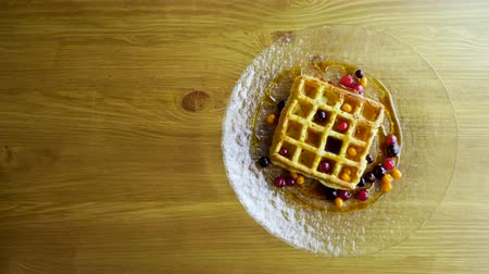 кафе : Sweet breakfast. Top view of viennese waffles with fresh berries, honey, syrup on a glass plate. 4K