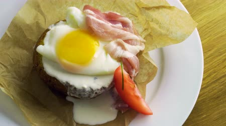poached egg : English breakfast. Close-up shot of poached egg and bacon on toast with fresh vegetables. 4K