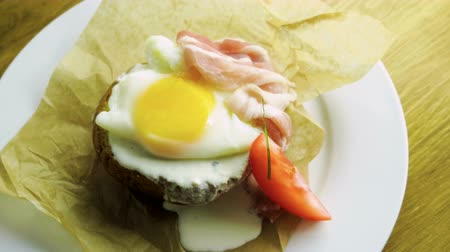 poached egg : English breakfast. Top view of poached egg and bacon on toast with fresh vegetables. 4K Stock Footage