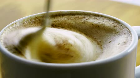 kafeterya : Cappuccino with cinnamon. Close-up shot of coffee cup with hot milk and heart pattern on top. 4K Stok Video