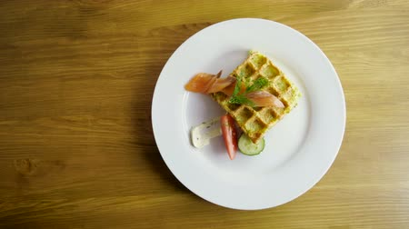 fumado : Potato casserole. Top view of womens hands putting a knife and fork next to a plate of pudding in shape of waffles with fresh cucumber, tomato, dill, smoked salmon, sour cream on the white plate. 4K Vídeos
