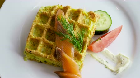 gofret : Potato casserole. Close-up shot of pudding in shape of waffles with fresh cucumber, tomato, dill, smoked salmon, sour cream on the white plate. 4K Stok Video