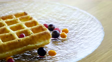 блин : Sweet breakfast. Close-up shot of viennese waffles with fresh berries, honey, syrup on a glass plate. 4K Стоковые видеозаписи
