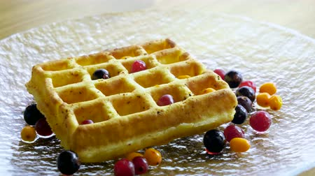 gofret : Sweet breakfast. Close-up shot of viennese waffles with fresh berries, honey, syrup on a glass plate. 4K Stok Video