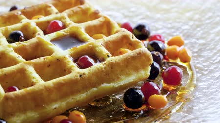 viennese : Sweet breakfast. Close-up shot of viennese waffles with fresh berries, honey, syrup on a glass plate. 4K Stock Footage