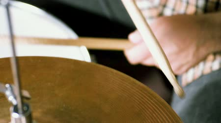 dobverő : Musical band. Group of musicians playing rock music on stage. Close-up shot of drummer playing the drums by hitting it with sticks. Slow motion. HD