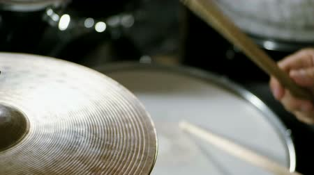 drumbeat : Musical band. Group of musicians playing rock music on stage. Close-up shot of drummer playing the drums by hitting it with sticks. Slow motion. HD