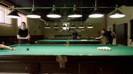 sinuca : Men playing billiards, hitting the balls with a cue into pockets on a billiard table. 4K Stock Footage
