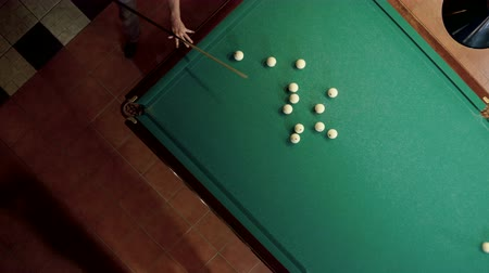 pallino : Top view of man playing billiards, hitting the balls with a cue into pockets on a billiard table. 4K