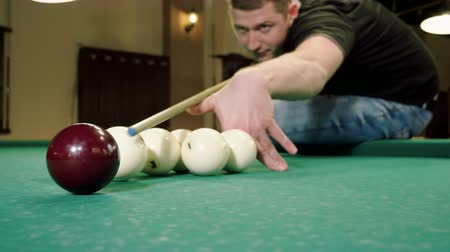 sinuca : Man playing billiards, hitting the balls with a cue into pockets on a billiard table. 4K