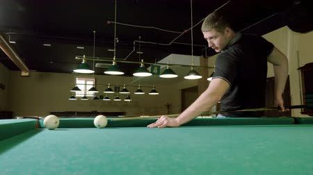 biljart : Man playing billiards, hitting the balls with a cue into pockets on a billiard table. 4K