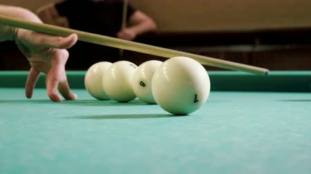 pallino : Close-up shot of hands of man playing billiards, hitting the balls with a cue into pockets on a billiard table. 4K