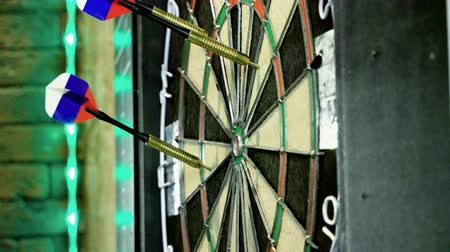 точность : Close-up shot of dart arrow hitting in target center of dartboard in game of darts. 4K Стоковые видеозаписи
