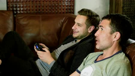 yarışma : Two men sitting on a leather couch, holding gamepad with both hands and having fun playing video game on console. 4K Stok Video