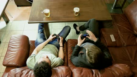 gameplay : Two men sitting on a leather couch, holding gamepad with both hands and having fun playing video game on console. 4K Stock Footage