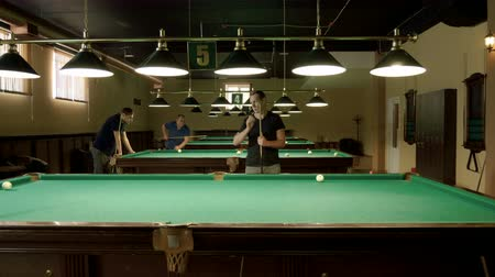 żyrandol : Men playing billiards, hitting the balls with a cue into pockets on a billiard table. 4K Wideo