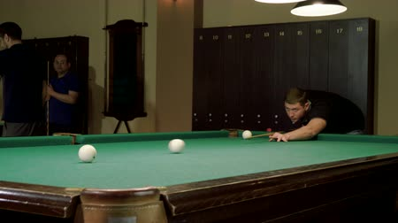 aim : Men playing billiards, hitting the balls with a cue into pockets on a billiard table. 4K Stock Footage