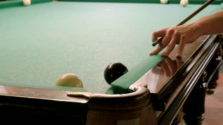 biljart : Men playing billiards, hitting the balls with a cue into pockets on a billiard table. 4K Stockvideo