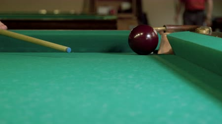 sinuca : Game of billiards. Close-up shot of billiard ball hitted by snooker cue falling into pocket on a billiard table. 4K