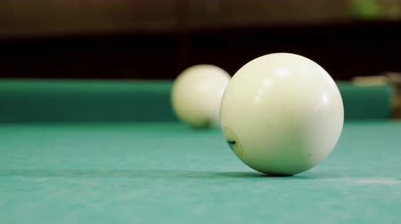 sinuca : Game of billiards. Close-up shot of cue hitting the white ball with number 7 into pocket on billiard table. 4K