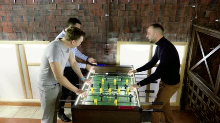 bola de futebol : Sport, game concept. Foosball. Three men playing a table football or kicker with miniature players. 4K