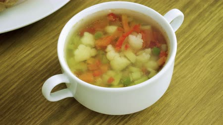 zupa groszek : Close-up shot of vegetable soup with cauliflower, green peas, carrots, bell pepper, potatoes on chicken broth. 4K