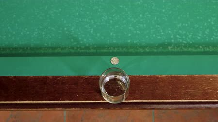 sinuca : Game of billiards. White billiard ball hitting the board of pool table, on which lying a coin and it bouncing into the glass. 4K
