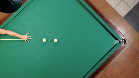 Top view of man playing billiards, hitting the balls with a cue into pockets on a billiard table. 4K