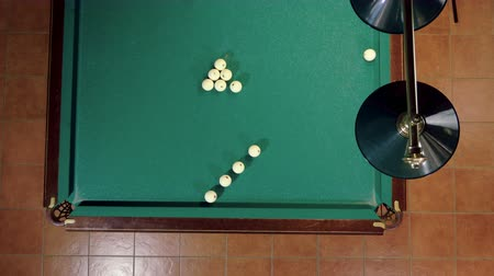 sinuca : Top view of man playing billiards, hitting the balls with a cue into pockets on a billiard table. 4K