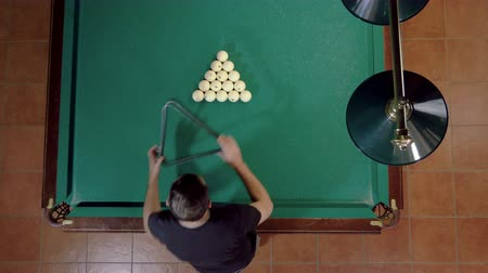 Top view of man playing billiards, breaking the balls with a cue into pockets on a billiard table. 4K Stock mozgókép