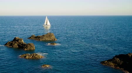 The yacht sailing in the Mediterranean sea. The rocky headland of Cabo de Palos. Landscape of Mediterranean coast in Spain. 4K