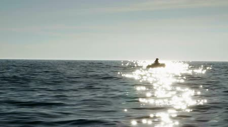 The dark silhouette of an inflatable motor boat and fisherman fishing in the sea. Slow motion. HD