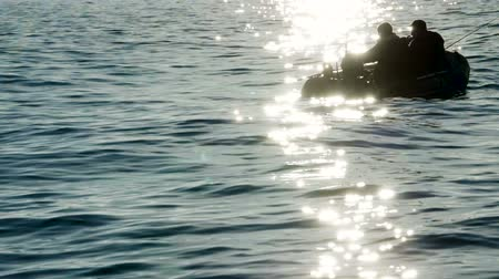 The dark silhouette of an inflatable motor boat and fishermen fishing in the sea. Slow motion. HD Dostupné videozáznamy