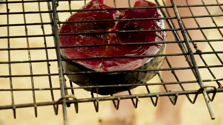 Close-up shot of cooking fish. Baking and roasting marinated fish on barbecue grill. Tuna grilled over charcoal. Slow motion. HD