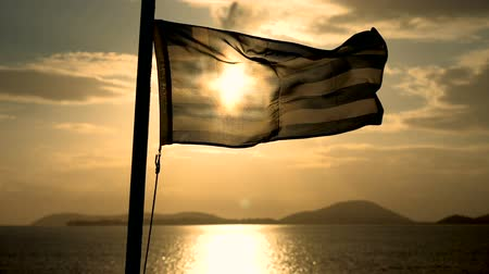 greece flag : The flag of Greece flying in the wind on a ship sailing on the sea at dusk. Slow motion. HD