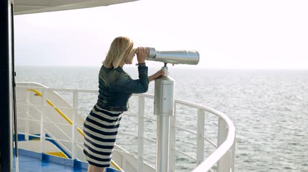 pont : Mature adult blonde woman standing on deck of cruise ship and looking through tourist binoculars at seascape. Slow motion. HD Stockvideo