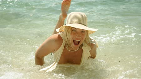 plavky : Beautiful happy woman dressed in swimsuit and straw hat posing on beach against calm sea. Slow motion. HD