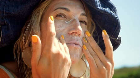 sunblock : Protection from the sun on vacation. Close-up shot of young blonde woman rubbing a sun cream, sunscreen or suntan lotion into skin on her face. Slow motion. HD