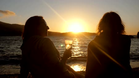 homokóra : Silhouette of two women sitting on shore of Mediterranean sea, drinking an alcoholic drink at sunset. Greece. Slow motion. HD