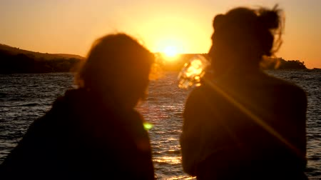 homokóra : Silhouette of two women sitting on shore of Mediterranean sea, drinking an alcoholic drink, looking at sea in the sunset. Greece. Slow motion. HD