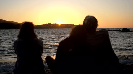 tourist silhouette : Rear view of three women sitting on shore of Mediterranean sea, talking, looking at sea in the sunset. Greece. Slow motion. HD